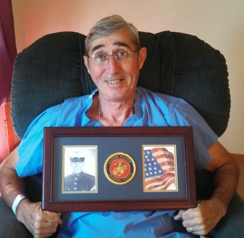 Man sitting in chair holds frame with black and white photo of self, Marine Corps emblem, and American flag image